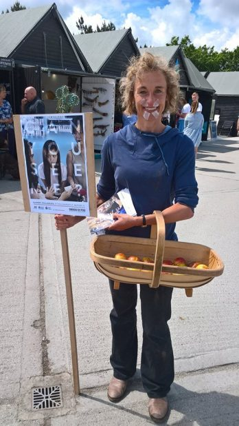 a-volunteer-dressed-as-a-fruit-picker-holding-a-basket-and-placard
